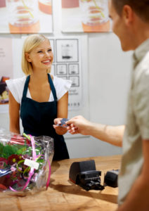 Smiling young florist accepting a credit card from a paying customer